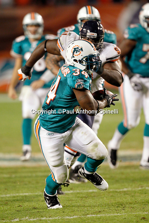 Miami Dolphins running back Ricky Williams (34) catches a late game pass and runs for extra yardage as the clock runs out in the fourth quarter of the NFL week 11 football game against the Chicago Bears on Thursday, November 18, 2010 in Miami Gardens, Florida. The Bears won the game 16-0. (©Paul Anthony Spinelli)
