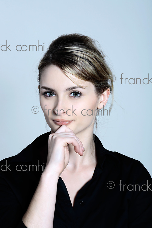 studio shot portraits of a young and cute and expressive woman on a blue grey background