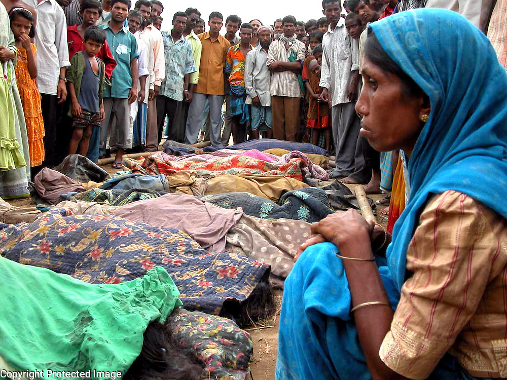 Pambuli Begum, right, and other unidentified villagers of Kala Pani look at bodies of people who died in a storm at Kala Pani about 300 kilometers (186 miles) from Gauhati, capital of northeastern Indian state of Assam, Wednesday, April 23, 2003.  A cyclone swept through Assam state, killing at least 36 people and injuring 1.500 others, police said Wednesday. (AP Photo/Shib Shankar Chatterjee)