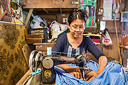 14 JUNE 2013 -  PATHEIN, AYEYARWADY, MYANMAR: A woman sews clothes in her stand in the market in Pathein, Myanmar. Pathein, sometimes also called Bassein, is a port city and the capital of the Ayeyarwady Region, Burma. It lies on the Pathein River (Bassein), which is a western branch of the Irrawaddy River. It's the fourth largest city in Myanmar (Burma) about 190 km west of Yangon.   PHOTO BY JACK KURTZ
