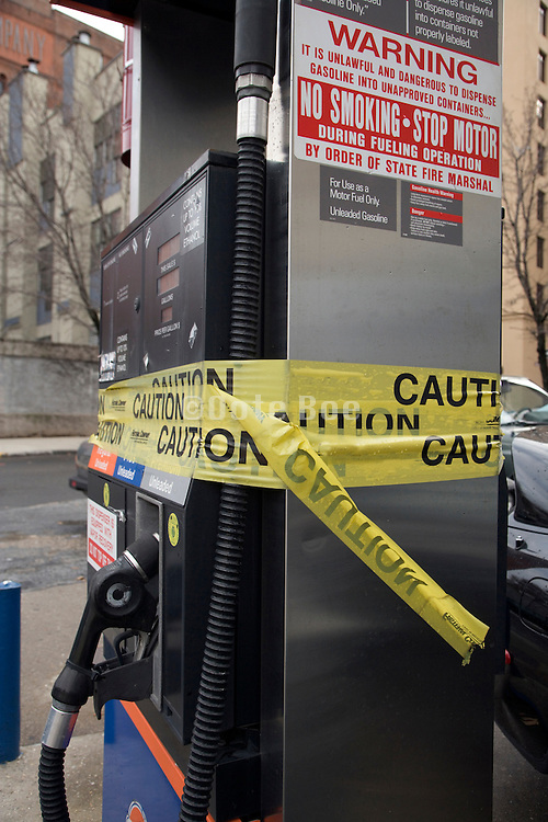 broken down gas pump station taped up with yellow caution tape