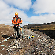 "Rope access technician Atli Þór Þorgeirsson working on the removal of safety nets, in the canyon ""Hafrahvammagljúfur"", at Kárahnjúkar dam area, Iceland. Safety nets were put up to prevent rockfall onto workers, working on the lower dam."