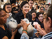 11 NOVEMBER 2016 - BANGKOK, THAILAND: YINGLUCK SHINAWATRA (left) sells a sack of rice to a woman at a rice distribution sale in the Bangkok suburbs. Yingluck Shinawatra, the former Thai Prime Minister deposed in a coup in 2014, has started selling rice directly to Thai consumers. She buys the rice from farmers at market prices and then sells it to urban consumers at the price she paid. She said she's doing it to help out farmers, who are trying to deal with depressed prices. Yingluck is facing prosecution on corruption related charges going back to a rice price support scheme her government used to try to help farmers in 2011 and 2012. Even after the coup, she is still personally popular and hundreds of people showed up to see her at the rice distribution point at a mall in Samut Prakan province, in suburban Bangkok.   PHOTO BY JACK KURTZ