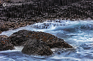 Waves crash into basalt at the Giant's Causeway in County Antrim, Northern Ireland