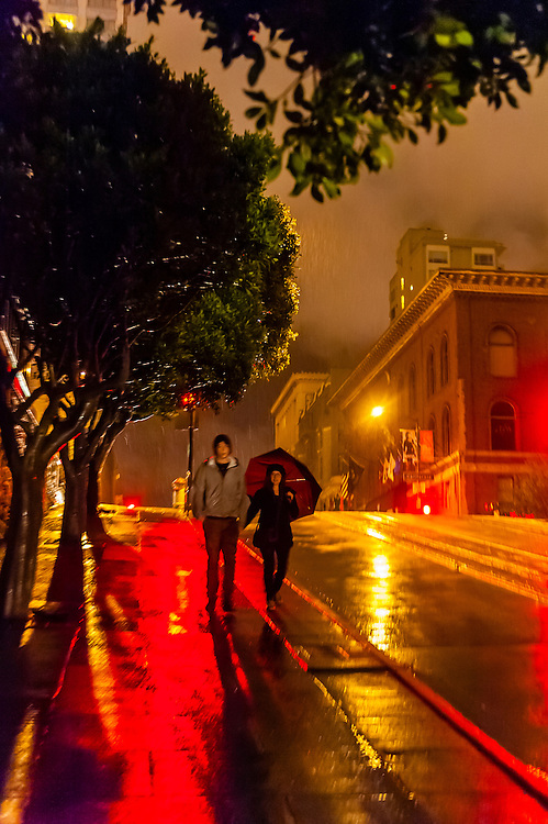 Couple walking on a rainy evening, Powell Street, San Francisco, California USA