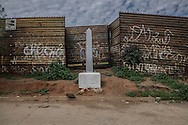 Border marker in front of US-built border wall marked with gang graffiti and a sign, posted by the National Program for the Protection of Migrants (Programa Nacional de Proteccion a Migrantes), warning about cliffs on the other side of the border in Tecate.  Baja California, Mexico.