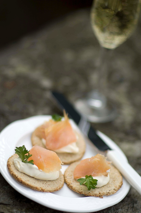A glass of wine and smoked salmon canapés, Organic Smoke House, Clunbury, Shropshire. Debbie and Michael Leviseur.
