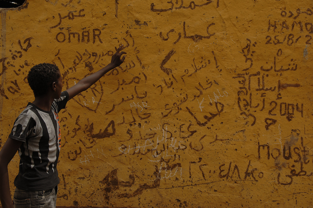 Boy shows wall markings in Elepantine Island on the Nile river, Egypt.