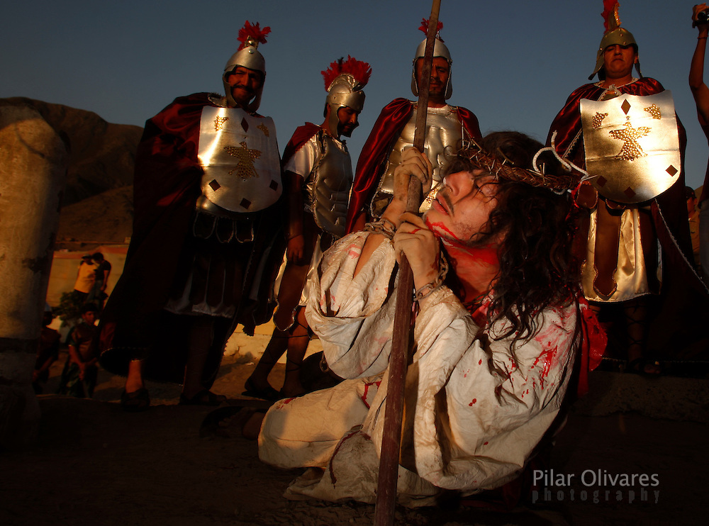 "An actor who is playing the role of Jesus Christ grimaces after being ""whipped"" by residents playing the role of Roman soldiers in an re-enactment of the crucifixion of Jesus Christ on Good Friday during Holy Week on the outskirts of Lima April 2, 2010."