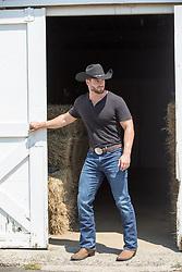 rugged cowboy opening up a barn door