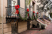 The ironwork balcony on a historic home decorated with bows and fir roping for Christmas in Savannah, GA.