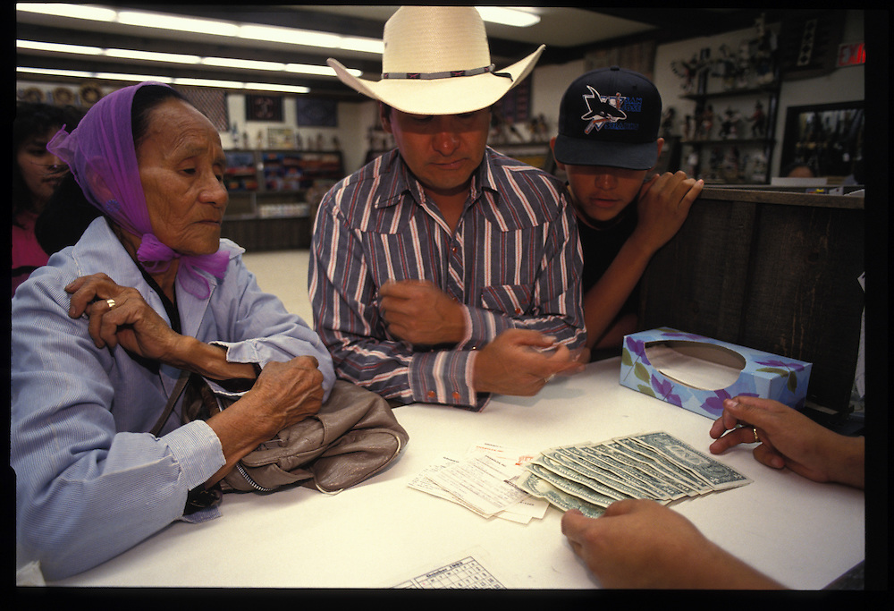 Irene McCabe, with her son Jerry and grandson Jared, cashes a Social Security check at Griswold's trading post in Tse Bonito.  Pawning is especially important to elderly Navajoos, to whom savings accounts are alien.