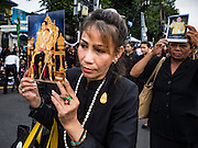 29 OCTOBER 2016 - BANGKOK, THAILAND:  People hold photos of the late Bhumibol Adulyadej, the King of Thailand, while they file into the Grand Palace to pay homage to His Majesty. Saturday was the first day Thais could pay homage to the funeral urn of the late Bhumibol Adulyadej, King of Thailand, at Dusit Maha Prasart Throne Hall in the Grand Palace. The Palace said 10,000 people per day would be issued free tickerts to enter the Throne Hall but by late Saturday morning more than 100,000 people were in line and the palace scrapped plans to require mourners to get the free tickets. Traditionally, Thai Kings lay in state in their urns, but King Bhumibol Adulyadej is breaking with tradition. His urn reportedly contains some of his hair, but the King is in a coffin,  not in the urn. The laying in state will continue until at least January 2017 but may be extended.      PHOTO BY JACK KURTZ