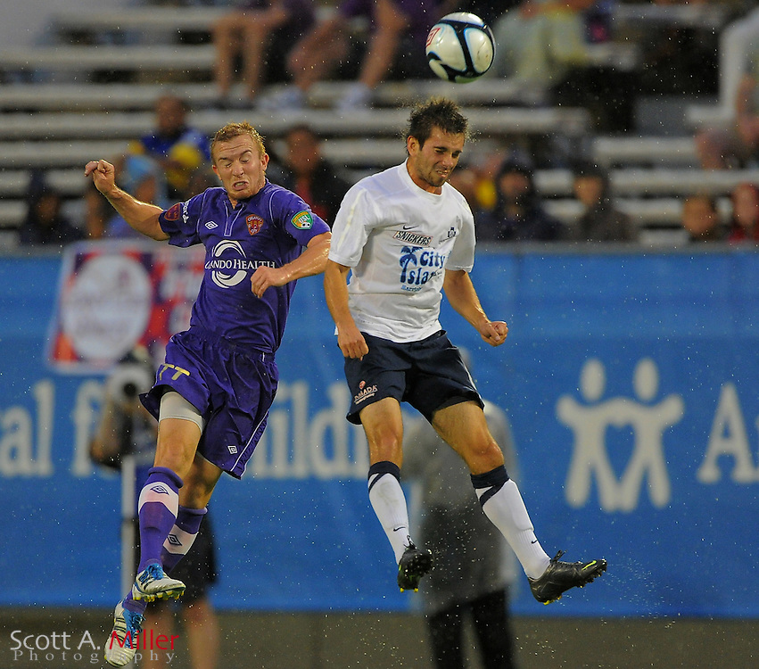 Orlando City Lions forward Jamie Watson (77) and Harrisburg City Islanders defender Andrew Marshall (5) go airborne for a ball during the Lions 3-0 win over the Islanders in their USL Pro game at the Citrus Bowl on June 22, 2012 in Orlando, Florida. ..©2012 Scott A. MIller