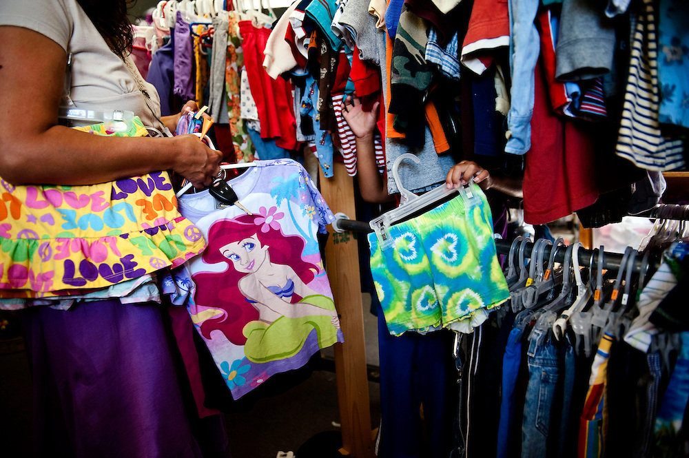 Keya, 5, holds out a pair of shorts she likes at a thrift shop in North Platte, NE. Having left their home in Rosebud, South Dakota quickly, Mary was only able to fill a few bags to take with them, leaving them with a very limited supply of clean clothing.