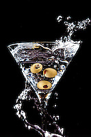A vodka martini splashes as olives are dropped in.