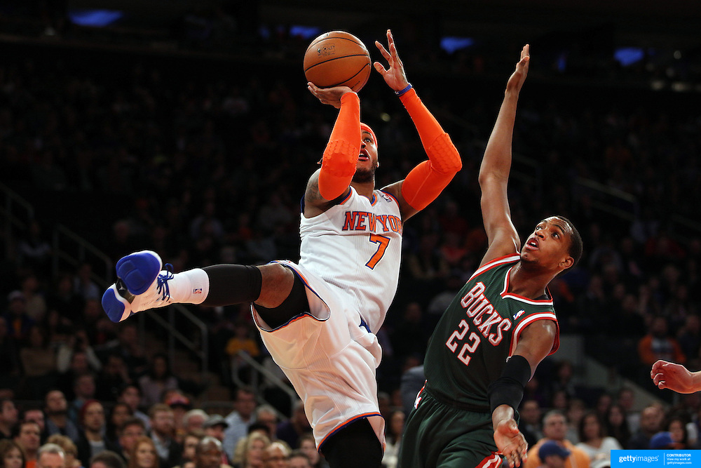 Carmelo Anthony, New York Knicks, shoots two past Khris Middleton, Milwaukee Bucks, during the New York Knicks vs Milwaukee Bucks, NBA Basketball game at Madison Square Garden, New York. USA. 15th March 2014. Photo Tim Clayton