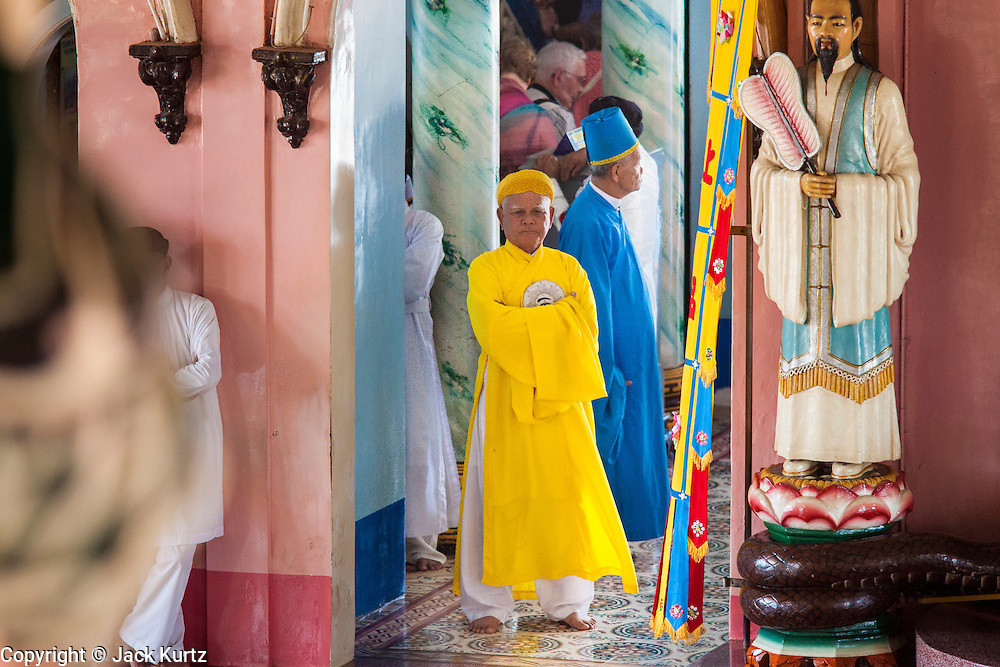 """29 MARCH 2012 - TAY NINH, VIETNAM:   Cao Dai clergy, in brightly colored robes, lead adherents into the prayer hall during the noon services at the Cao Dai Holy See in Tay Ninh, Vietnam. Cao Dai (also Caodaiism) is a syncretistic, monotheistic religion, officially established in the city of Tây Ninh, southern Vietnam in 1926. Cao means """"high"""" and """"Dai"""" means """"dais"""" (as in a platform or altar raised above the surrounding level to give prominence to the person on it). Estimates of Cao Dai adherents in Vietnam vary, but most sources give two to three million, but there may be up to six million. An additional 30,000 Vietnamese exiles, in the United States, Europe, and Australia are Cao Dai followers. During the Vietnam's wars from 1945-1975, members of Cao Dai were active in political and military struggles, both against French colonial forces and Prime Minister Ngo Dinh Diem of South Vietnam. Their opposition to the communist forces until 1975 was a factor in their repression after the fall of Saigon in 1975, when the incoming communist government proscribed the practice of Cao Dai. In 1997, the Cao Dai was granted legal recognition. Cao Dai's pantheon of saints includes such diverse figures as the Buddha, Confucius, Jesus Christ, Muhammad, Pericles, Julius Caesar, Joan of Arc, Victor Hugo, and the Chinese revolutionary leader Sun Yat-sen. These are honored at Cao Dai temples, along with ancestors.   PHOTO BY JACK KURTZ"""