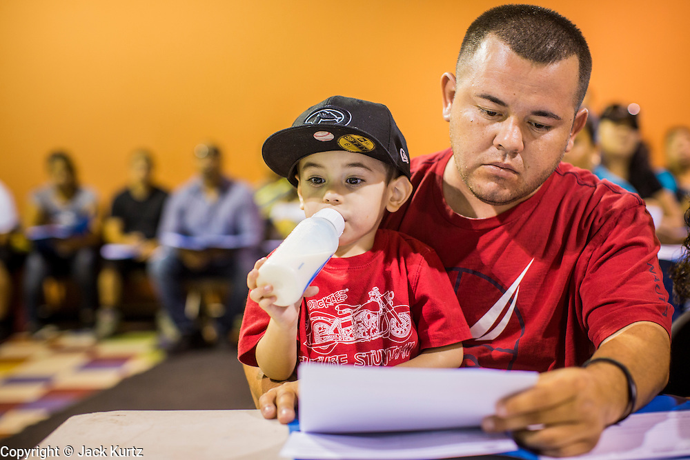 "18 AUGUST 2012 - PHOENIX, AZ: A man holds his son while he goes over paperwork related to ""deferred action"" during a deferred action workshop in Phoenix. More than 1000 people attended a series of 90 minute workshops in Phoenix Saturday on the ""deferred action"" announced by President Obama in June. Under the plan, young people brought to the US without papers, would under certain circumstances, not be subject to deportation. The plan mirrors some aspects the DREAM Act (acronym for Development, Relief, and Education for Alien Minors), that immigration advocates have sought for years. The workshops were sponsored by No DREAM Deferred Coalition.  PHOTO BY JACK KURTZ"