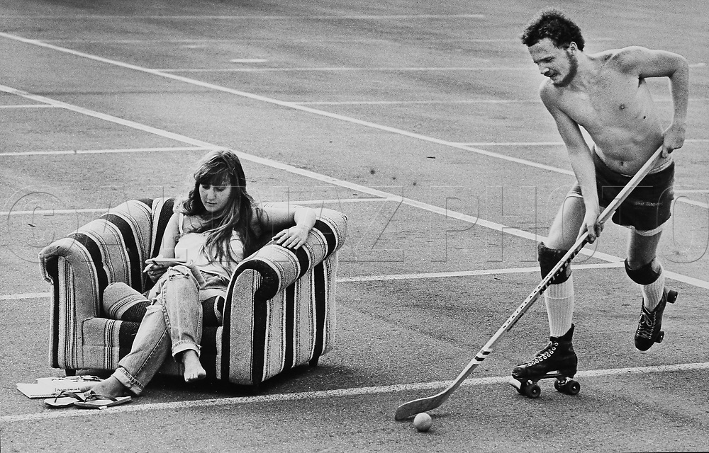 Nadine Shocet studies for her political science finals while her boyfriend, Kevin Fay, practices street hockey at a campus parking lot at the University of Florida. The two loaded up the sofa chair and brought it out to the parking lot for fun in 1982.