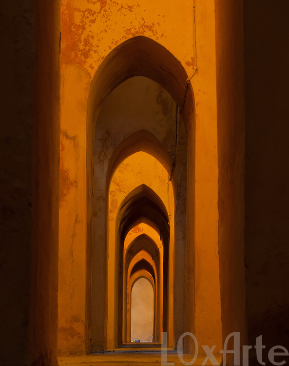 Arches and lights creating a pattern in the Alcazar of Seville, Spain.