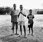 KAKUMA, KENYA - JANUARY 17, 2008: Portrait of three refugee boys. In 2003, the Comprehensive Peace Agreement was signed between the Sudanese nationalists and the Sudan People's Liberation Army, granting the predominantly Christian Sudanese in the south independence from Muslim regime in Khartoum. Despite the agreement, Central Africa's spiritual, political, and cultural climates remain in a state of unrest. Violence and persecution persists as rebel factions and various ethnic cleansing efforts divide north from south, forcing thousands of Sudanese natives into the southern part of the country and across the border into northern Kenya.