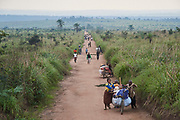 Men and women walk along a road between the village of Lumbambala and the town of Mwene-Ditu, Province of Lomami, Democratic Republic of Congo on September 16, 2017. Many of the villagers fled their homes into the bush in March/April 2017 as the Kamwina Nsapu militia battled with security forces in the villages. When CRS visited the village in July, 2017, many of the villagers had still not returned. When they eventually returned, many found their homes had been burnt down. Many of the villagers are living in makeshift shelters while they attempt to rebuild them. To assist these returnees, CRS teams interview each household to determine if it will receive assistance. The ARCC III project has been implemented in four zones, with each household receiving between $5-$25 depending on their vulnerability. The program also involves an awareness component on how to potentially spend the the money with focus on nutrition, education and healthcare. As part of the monitoring and evaluation component, CRS teams return 1 month later to the zone and interview beneficiaries to learn how they have spent the money.