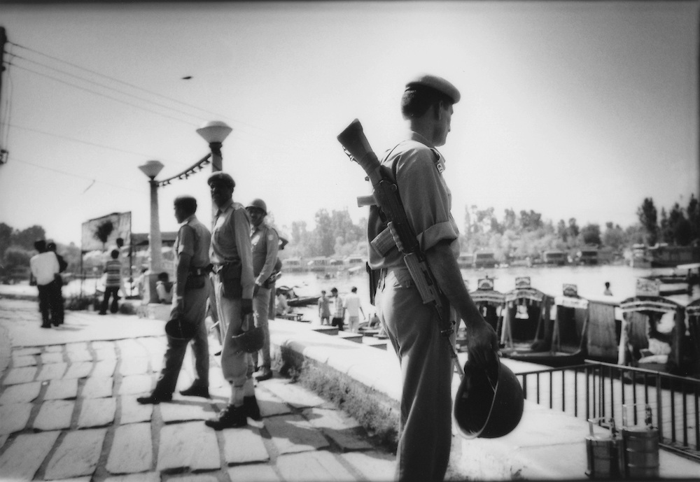 Patrolling Indian soldiers, armed with automatic weapons, watch over majority Hindu tourists along Dal Lake boat landing.  Tourism is Kashmir's primary source of income.  Tourist industry numbers, particularly the number of foreign tourists,  have been a mere fraction of what they had been before the current trouble beginning in the 1990's.