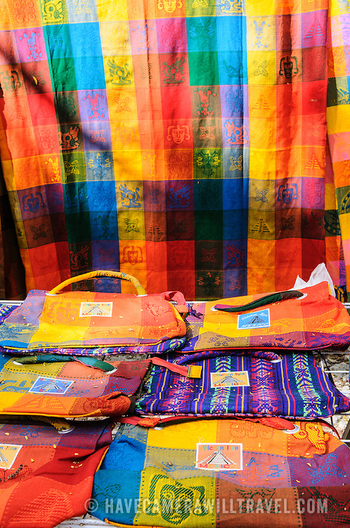 Brightly colored woven textiles for sale at the market stalls selling local souvenirs and handicrafts to tourists visiting Chichen Itza Mayan ruins archeological site in Mexico.