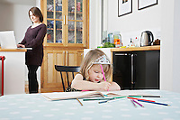 Girl (3-4) drawing in book mother using laptop in background