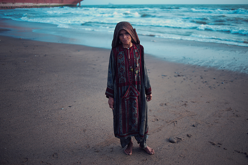 Metal Scavenger Darba, 45 years old at the Gaddani Ship Breaking Yard, Balochistan Province, Pakistan on August 16, 2011. She is from Balochistan, a widow and has two children. She lives 20km away and makes money from searching in the waters for small fragments of metal from the ships being broken up along the stretch of beach. She makes money off she finds, 30 Pakistani Rupees ( 25US cents) per kilogram of metal found.