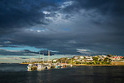 Golden sunlight shines on the docked fishing boats as storm clouds hang overhead, at Riverton, Southland, New Zealand.