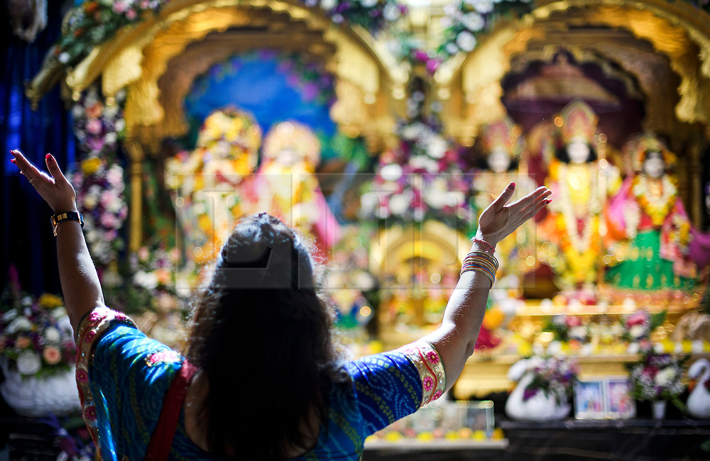 © Licensed to London News Pictures. 02/09/2018. Aldenham, UK. A woman worships in front of Statues of Hindu deities at Bhaktivedanta Manor Temple in Aldenham, Hertfordshire during the Janmashtami Hindu festival. Janmashtami is an annual Hindu festival that celebrates the birth of Krishna. Bhaktivedanta Manor, the venue fo the event, was donated to the Hare Krishna movement in February 1973 by former Beatle George Harrison. Photo credit: Ben Cawthra/LNP
