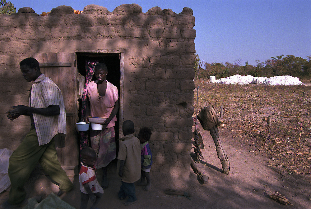 Cotton farmers in their home amid their fields of harvested cotton near a remote village. Despite a record yield, West African cotton producers are being driven deeper into poverty and debt by US and European cotton subsidies..Karandasso Sambla, Burkina Faso. 12 December 2003..Photo © J.B. Russell