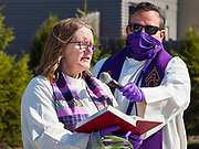 "05 APRIL 2020 - DES MOINES, IOWA:  Rev. RUSSELL LACKEY, right, holds the microphone for Rev. BONNIE PARKER, who read from the Bible, during a drive through Palm Sunday service sponsored by Luther Memorial Church on the campus of Grand View University in Des Moines. About 150 people attended the service. They remained in their cars while the ministers read a short passage from the Bible, handed out palms and blessed them. On Sunday, 05 April, Iowa reported 868 confirmed cases of the Novel Coronavirus (SARS-CoV-2) and COVID-19. There have been 22 deaths attributed to COVID-19 in Iowa. Restaurants, bars, movie theaters, places that draw crowds are closed until 30 April. The Governor has not ordered ""shelter in place"" but several Mayors, including the Mayor of Des Moines, have asked residents to stay in their homes for all but essential needs. People are being encouraged to practice ""social distancing"" and many businesses are requiring or encouraging employees to telecommute.        PHOTO BY JACK KURTZ"