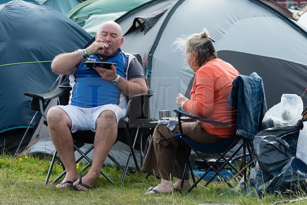 © Licensed to London News Pictures. 13/06/2015. Isle of Wight, UK.  Festival goers eat breakfast by their tent at Isle of Wight Festival 2015 on the morning of Saturday Day 3.  Yesterday suffered torrential rain all afternoon and evening, after a first day of warm sun.  This years festival include headline artists the Prodigy, Blur and Fleetwood Mac.  Photo credit : Richard Isaac/LNP
