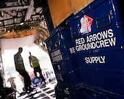 Members of the 'Red Arrows', Britain's Royal Air Force aerobatic team, supervise the loading of spares and personal effects into a C-130 Hercules aircraft before the two-day journey from RAF Scampton to RAF Akrotiri in Cyprus. Surrounded by heavy-duty flight-spares, survival equipment boxes and a tyre for a Hawk jet aircraft, the Hercules looms large in the overcast sky. The team complete their winter training schedule in Cyprus. The Red Arrows pilots fly their own jet aircraft to air shows but when requiring the support of ground crew  they borrow a transporter to fly behind the main airborne squadron. 10 tons of spares and personal effects are shipped for a six-week stay.