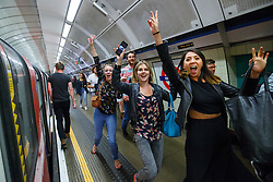 © Licensed to London News Pictures. 20/08/2016. London, UK. Tube passengers celebrate arriving Brixton after travelling on the night tube service of Victoria line in London for the first time on 20 August 2016. Transport for London started a 24-hour Tube service on Victoria and Central lines as demand has soared over recent years, with passenger numbers on Friday and Saturday nights up by around 70 per cent since 2000. The plan was announced in November 2013 and intended to begin in September 2015, but strikes over pay delayed the start by nearly another year. Photo credit: Tolga Akmen/LNP