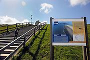 Nederland, Westkapelle, 15-4-2008..De kunstmatige zeewering van dit deel van de zeeuwse kust is de hoogste van het land. De zeedijk is aangelegd na de watersnoodramp in 1953, ter vervanging van de zwakke duinen en moet zeeland behoeden voor overstroming tijdens storm en hoogwater of springvloed. Een man en een vrouw zitten op een bankje en genieten van het uitzicht...Foto: Flip Franssen