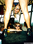 Man smiling through a pair of girls legs Ibiza 1999
