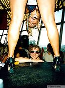 Man smiling through a pair of girls legs Ibiza 1999