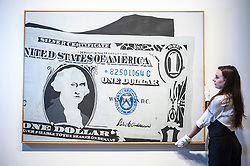 "© Licensed to London News Pictures. 08/06/2015. London, UK. A Sotheby's technician shows ""Silver Certificate"" by Andy Warhol (est. £13m - £18m), at the preview of ""To the Bearer on Demand"", a private collection of 21 works inspired by the US dollar, including Andy Warhol masterpieces, which will be auctioned on 1 and 2 July.  The collection is estimated to realise £50 million.  The painting on show is the artist's very first painting in his series of dollar paintings, and the only one painted entirely by hand. Photo credit : Stephen Chung/LNP"