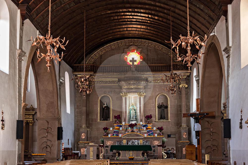Interior of the Templo de Nuestra Señora del Sagrario church with a barrel wooden ceiling and copper chandeliers in Santa Clara del Cobre, Michoacan, Mexico.