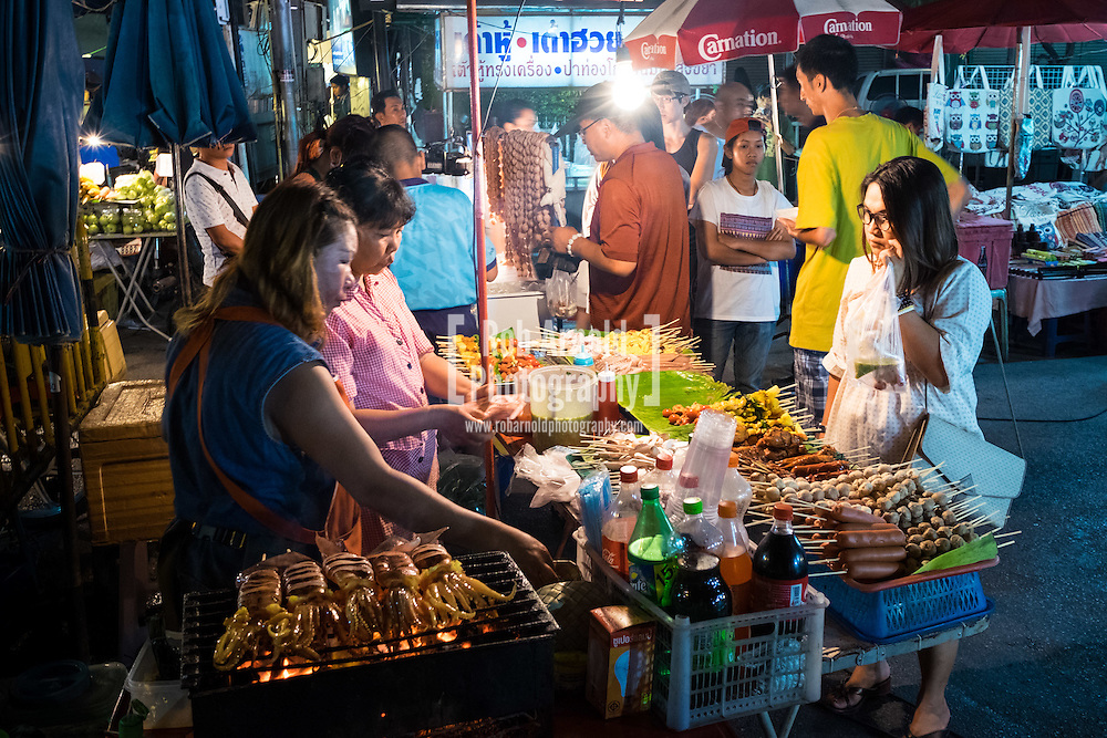 A food stall selling grilled meats and fish at the calm and atmospheric walking night market along Wualai Road in Chiang Mai, Thailand.