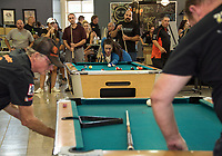 Cyndy Flynn lines up her shot during scotch doubles with her husband Shawn Flynn looking on during Laconia Harley Davidson's Pool Tournament Sunday afternoon to benefit the Children's Auction.  (Karen Bobotas/for the Laconia Daily Sun)