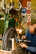 Marco Tavano checks  refurbished turbine blades for a steam turbine cooling tower.  Fausto Samadello sharpens a drill bit in the background. SARPOM refinery in  Trecate, Italy