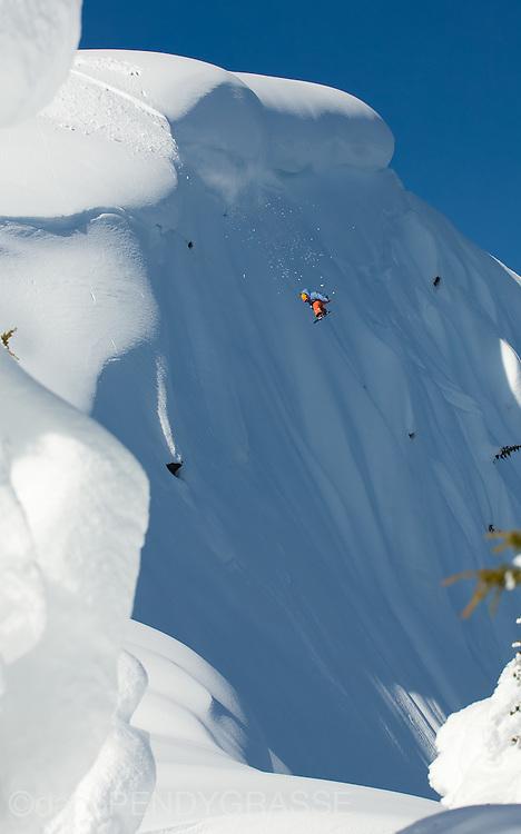Professional snowboarder Eric Jackson flies over a steep mountain face near Terrace, British Columbia, Canada.