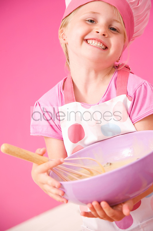 Close up of a smiling young girl holding a baking bowl and a whisk