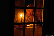 Colonial woman looking out the window past a candle into the night.  Palace Kitchen at Colonial Williamsburg. Photo by David M. Doody.