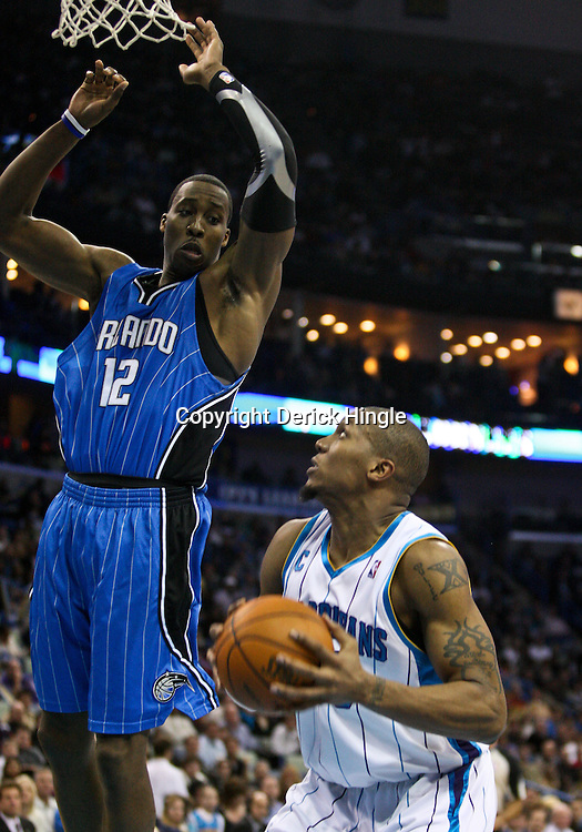 Feb 26, 2010; New Orleans, LA, USA; Orlando Magic center Dwight Howard (12) defends against New Orleans Hornets forward David West (30) during the second half at the New Orleans Arena. The Hornets defeated the Magic 100-93. Mandatory Credit: Derick E. Hingle-US PRESSWIRE